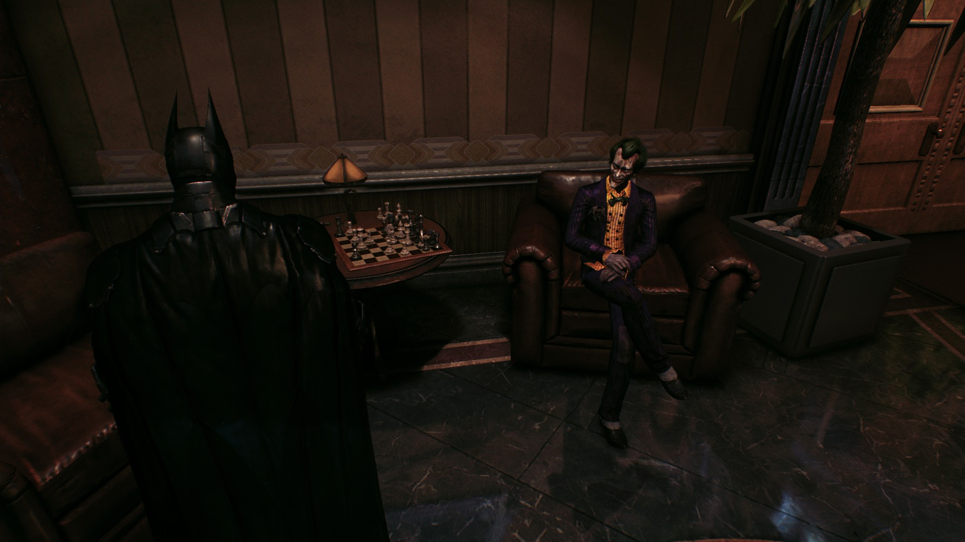 Joker, as a figment of Batman's imagination, sits of a chair in Wayne Tower. (There are a lot of hallucinations in this game.)