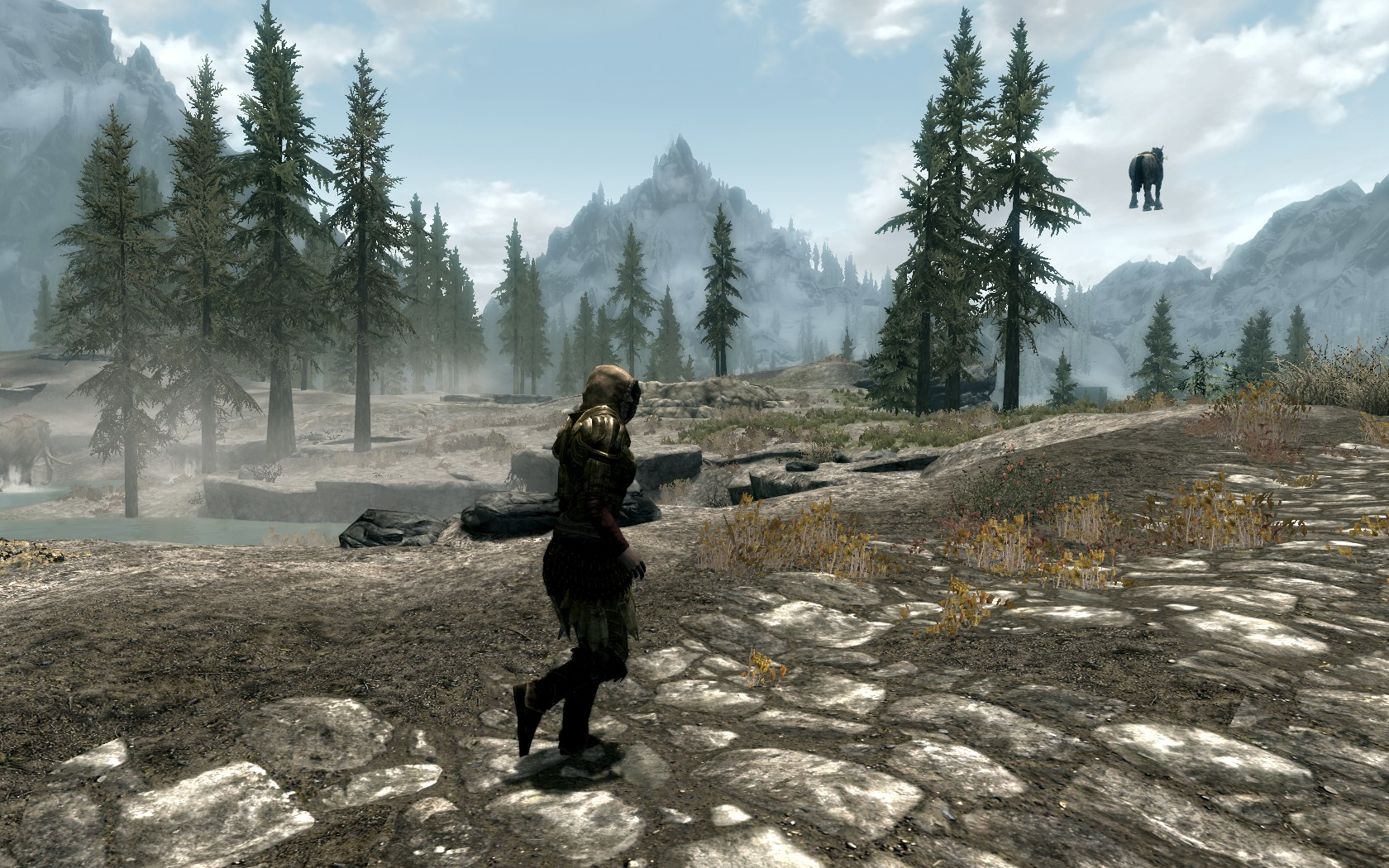 A screenshot from Skyrim shows a character chasing a horse flying off into the sky along a wilderness road.